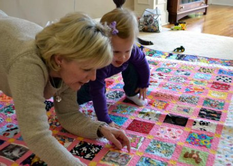 Grandmother And Child Looking At Quilt